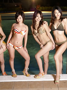 Fours sexy Asians posing in front of swimming pool