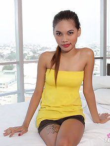 Cute babe opens her yellow dress and sleeping on bed with naked body