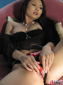 Beautiful Risa puts vibrator on clitoris between spread and sexy legs.