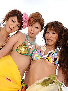Lusty hot girls pose in group in their bikinis and have fun on the set