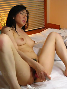 Horny Emiko Koike uses her sex toy in the bedroom in solo session